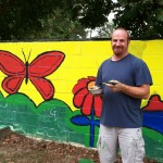 Prof. Rich Curtis giving a facelift to the playground mural at Thomasville Community Resource Center.
